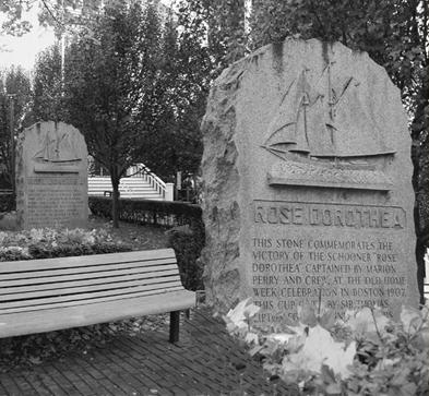 A black and white image of a memorial stone in a park